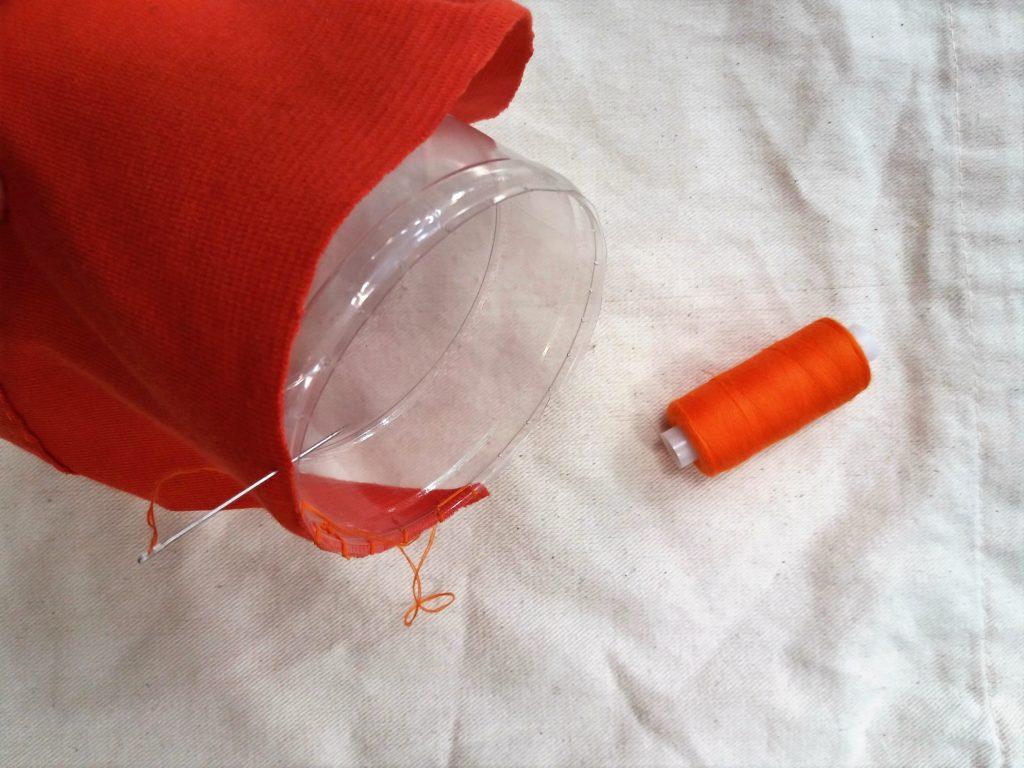 Dłuższy brzeg tkaniny bez zakładki szyty do brzegu butelki