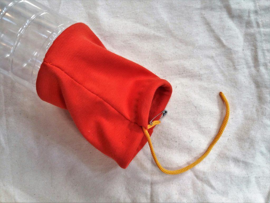 W zakładkę w tkaninie wciągnięty sznurek za pomocą agrafki